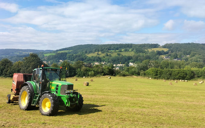 Cotswold contractors  with Round baler at Upton Saint Leonards