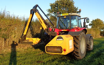 Jds agricultural contracting with Hedge cutter at United Kingdom