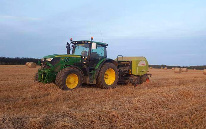 Dan hirst agricultural contractors  with Round baler at United Kingdom